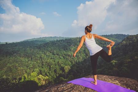 Asian woman doing yoga on a mountain cliff Stock Photo