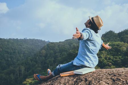 Viaje de hombre asiático relajarse en las vacaciones. asientos relajarse leer libros en acantilados rocosos. En el Moutain. En Tailandia Foto de archivo