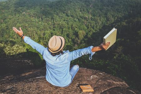 Aziatische mens die een boek en met open wapens op bergklip houdt