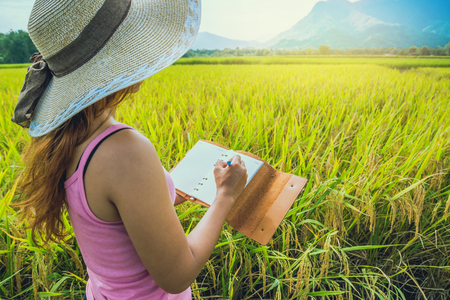 Asian women relax in the holiday. Write a note in the notebook. Write a study of natural garden garden.