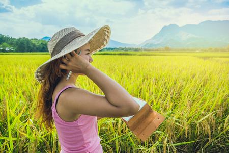 Aziatische vrouwen ontspannen in de vakantie. Schrijf een notitie in het notitieboek. Schrijf een studie van natuurlijke tuin tuin. Stockfoto