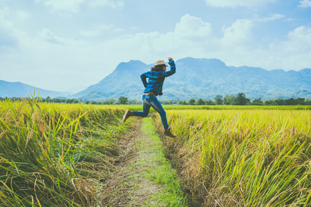 Asian man travel relax in the holiday. Jump natural touch mountain field. Jump stand glad middle field rice. Thailand