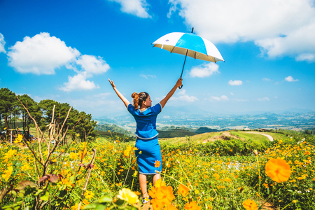 Asian women travel sleep relax. women hill tribe umbrella stand in the field of flowers. Thailand