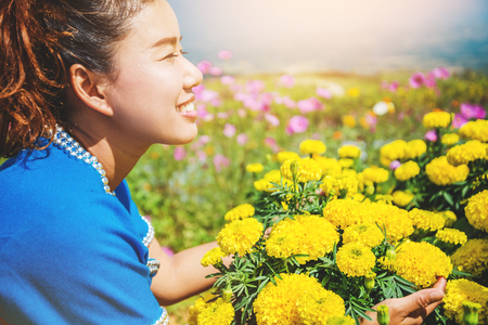 Asian women travel sleep relax. women hill tribe flower sitting in the field of flowers Tagetes erecta. Thailand