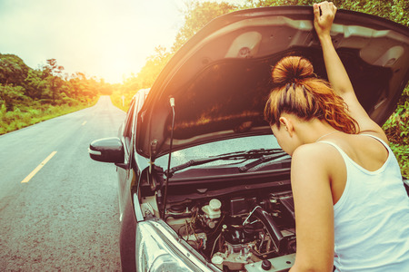 Asian women the car is broken road. Open the bonnet, check engine