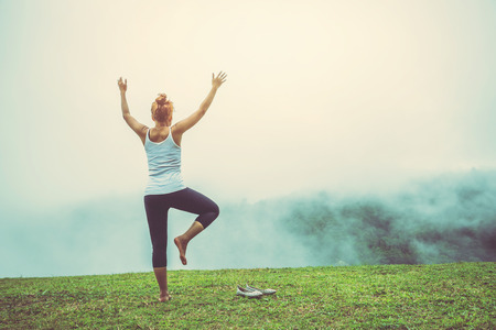 Asian women relax in the holiday. Play if yoga, natural caves, forests, mountains and mist. Stock Photo