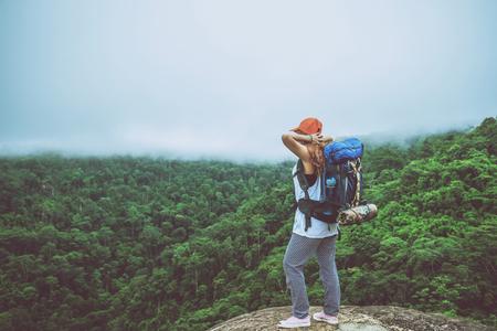 Las mujeres asiáticas viajan a relajarse en las vacaciones. Parado en la montaña en un acantilado rocoso. Tailandia Foto de archivo - 91716674