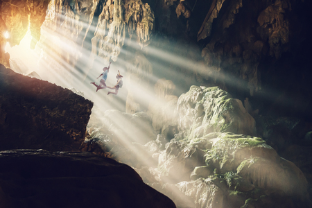 Lover women and men asians travel relax in the holiday. Jump cliff in the cave inside stalagmite caves in Asia, Laos Stock Photo