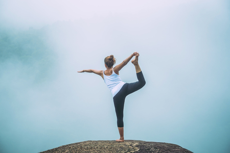 Asian women relax in the holiday. Play if yoga. On the Moutain rock cliff
