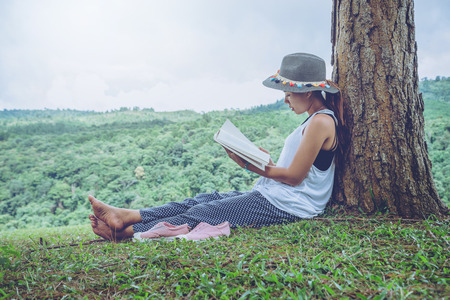 Asian women relax in the holiday. Sit read books on grassland in the park.