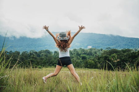 Asian women travel relax in the holiday. Jump on a green pasture. Imagens