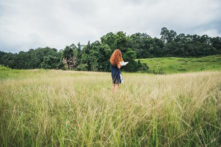 Aziatische vrouwen ontspannen in de vakantie. lees een boek over een groene weide. Stockfoto