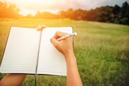 ノートの手書きは休日にリラックスします。緑の牧草地で。