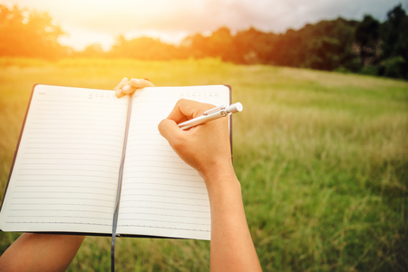 Handwriting on notebook relax in the holiday. on a green pasture.