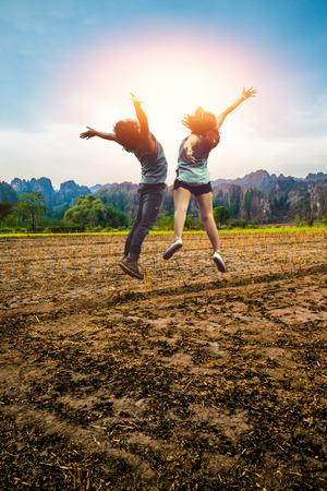 아시아 남성과 여성 애인 점프 여행 긴장. 시골 풍경입니다. 절기에있는 분야 자연적인 바위 같은 산