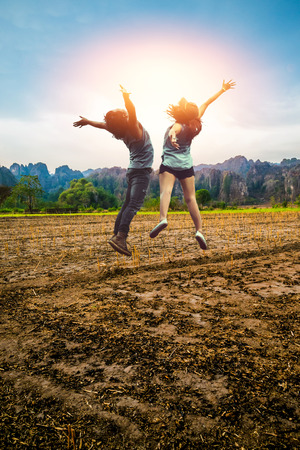 Asian men and women Lover jump travel relax. Rural landscape. Fields in season Natural rocky mountains