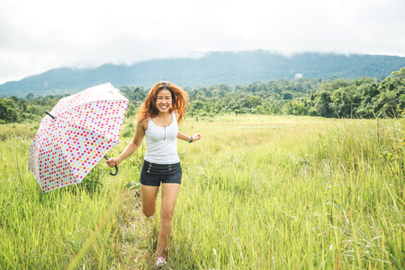 Asian women travel relax in the holiday. Running umbrella sunshine on a green pasture. Imagens