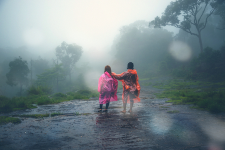 Lover Men and women Asia travel relax. walk in the forestrainy season. puhinrongkla Thailand