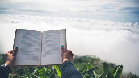 손 여자 휴식 아침 책 좋은 날씨 하늘 읽기 안개. 산에서 아침의 분위기.