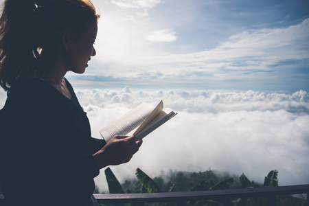 Women relax Read morning book good weather sky Mist. On the mountains, the morning atmosphere. Stock Photo
