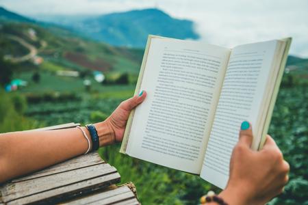 손을 잡고 책을 읽는 여성. 아침의 분위기 산은 안개가 자욱하다. phetchabun phutubberg 태국 스톡 콘텐츠