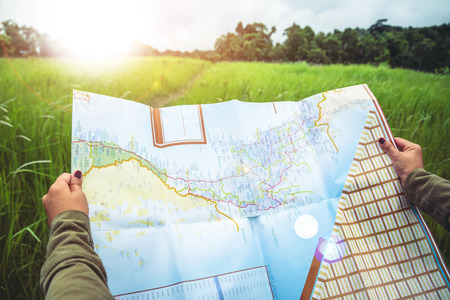 woman  travel. Asian women's hand catches a map of travelNatural forest on the grassland 스톡 콘텐츠