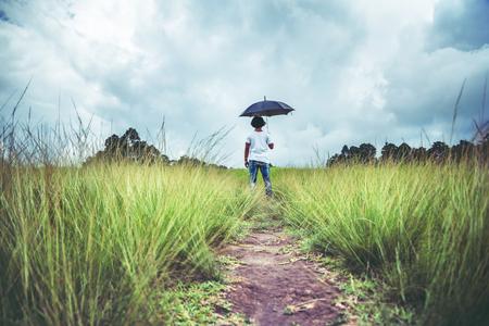 man standing umbrella On the green meadow in the rainy season. Asian man Stock Photo