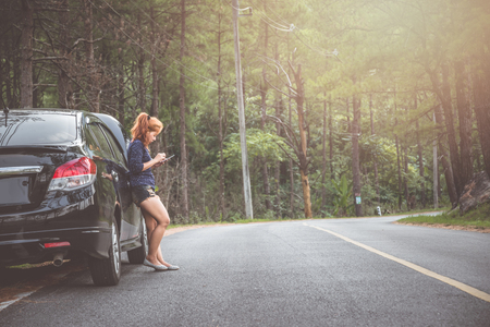 Women use the phone to contact broken car.
