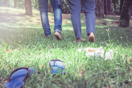 Couple women with men walking on grass in natural garden