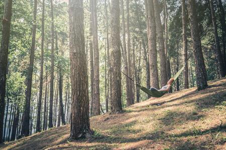 잠자는 여자 긴장. 그물 침대에서. 공원의 자연 환경에서 스톡 콘텐츠