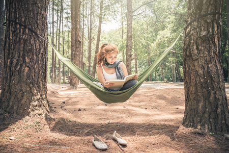 읽기 앉아 여자입니다. 그물 침대에서. 공원의 자연 환경에서