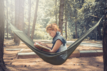 Women sitting reading. In the hammock. In the natural atmosphere in the park