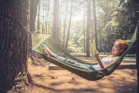 여자 독서 자고. 그물 침대에서. 공원의 자연 환경에서