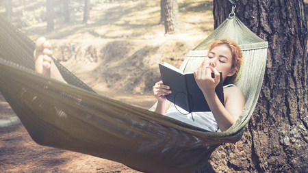 Sleeping women write notes. In the hammock. In the natural atmosphere in the park Stock Photo