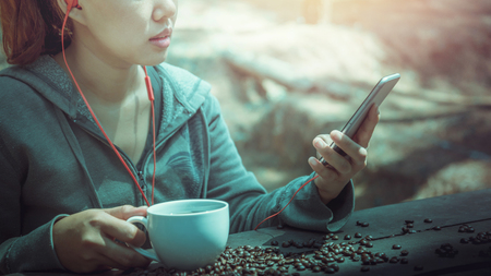 Women drink coffee Play mobile phone On the wooden table floor there is a coffee bean. Stok Fotoğraf - 91611636