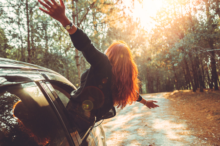 Woman driving a car traveling happily. Stock Photo