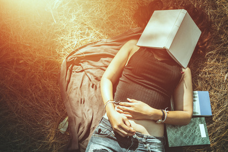 Woman relaxing reading in park. holiday Sleep rest in reading. Stock Photo