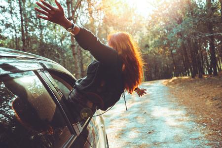 Woman driving a car traveling happily. Foto de archivo