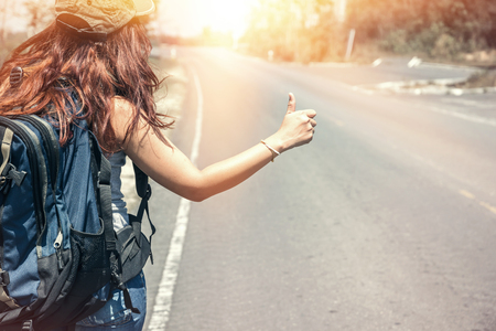 Women backpacking travel stand waving car. Surfing holidays Stock Photo
