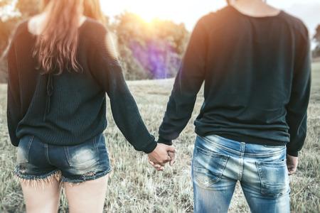 Lovers walk hand in hand on romantic evening sun, romantic atmosphere.