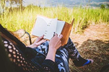 Aziatische vrouwen reizen ontspannen in de vakantie. kamperen op de berg. zit schrijf een briefje op de stoel. Thailand