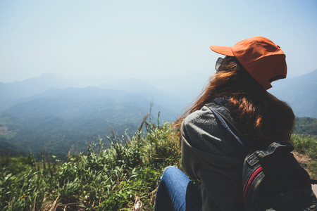 Asian women travel relax in the holiday.  Sit and watch landscape on the Moutain. Mountain Park happily. In Thailand Imagens