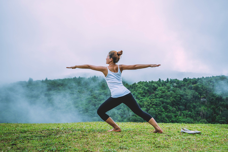 Asian women relax in the holiday. Play if yoga, natural forests, mountains and mist.
