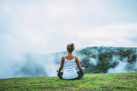 Asian woman relax in the holiday. Play if yoga, natural forests, mountains and mist.
