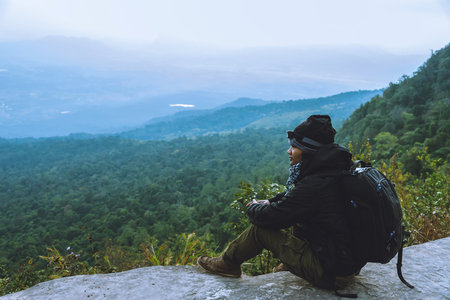 Men asians travel relax in the holiday. Admire the atmosphere landscape on the Moutain. Mountain Park happily. In Thailand