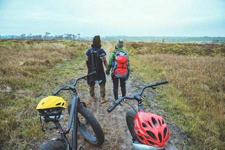Asian lover women and men Travel photograph nature. Travel relax ride a bike Wilderness in the wild.Stand on the line. In the meadow in the woods. Thailand  Stok Fotoğraf