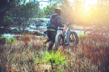 Asian man travel  Nature. Travel relax. ride a mountain bike Wilderness in the wild. Thailand