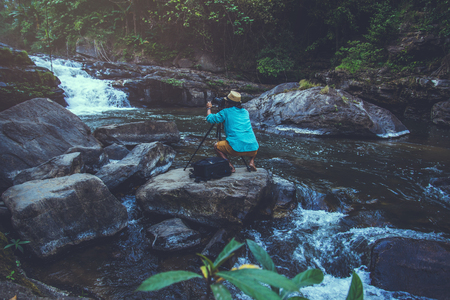 Asian man travel nature. Travel relax. Photograph waterfall travel. In the summer. Thailand
