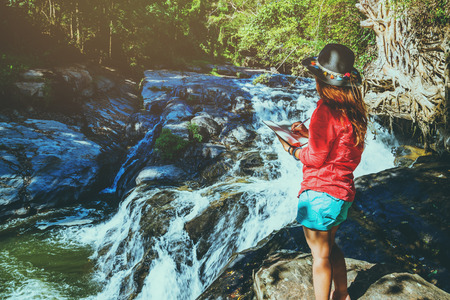Asian woman travel nature. Travel relax. Study read a book. Nature Education Write a note At Waterfall Use summer. In Thailand