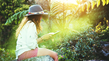 Asian woman travel nature. Travel relax. Study read a book. Nature Education Write a note At public park in summer. In Thailand Stock Photo